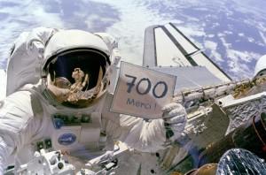 """L'astronaute Dale Gardner, tenant une affiche """"For Sale (à vendre) sur la photo originale, après avoir récupéré deux satellites qui avaient été placés sur de mauvaises orbites. (Crédit: NASA)"""